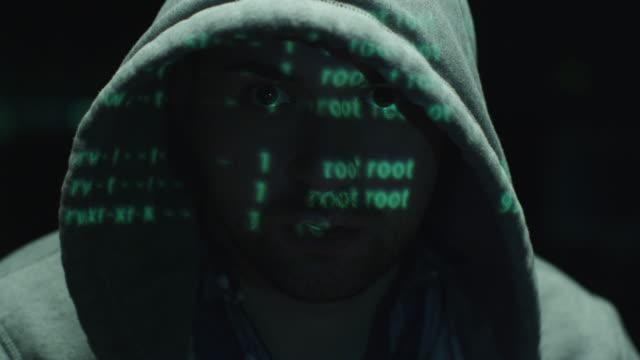 Macho hacker trabajando con una computadora mientras verde código caracteres reflexionar sobre su rostro de oficina en una sala oscura. - vídeo