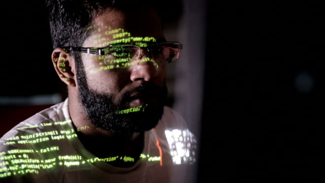 male hacker works on a computer with data on screens - minacce video stock e b–roll