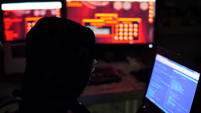 male hacker works on a computer with data on screens - anonymous hackers stock videos and b-roll footage