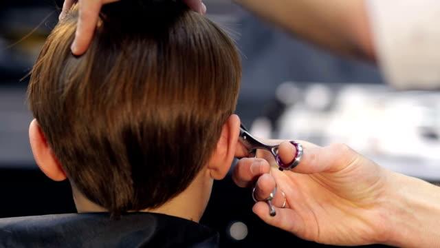 Male hairdresser cut child hair in barbershop. video