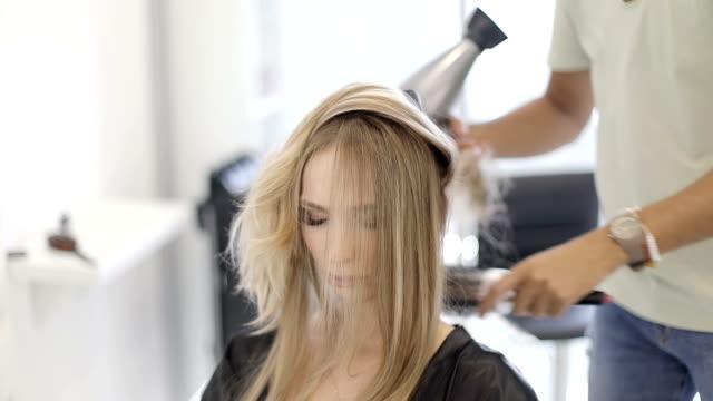 ein männlicher friseur trocknet lange haare blonde fön in einem modernen beauty-salon. - haartönung stock-videos und b-roll-filmmaterial