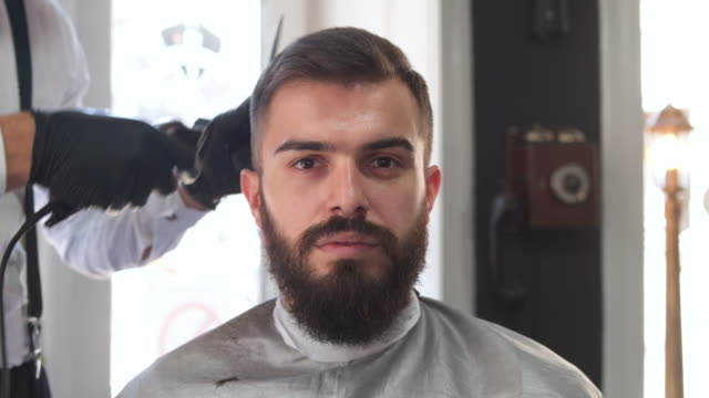 Male hairdresser giving a haircut in his barber shop