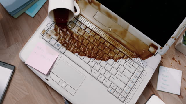 SLO MO LD Male hand accidentally knocking over a cup of coffee and spilling it on his laptop video