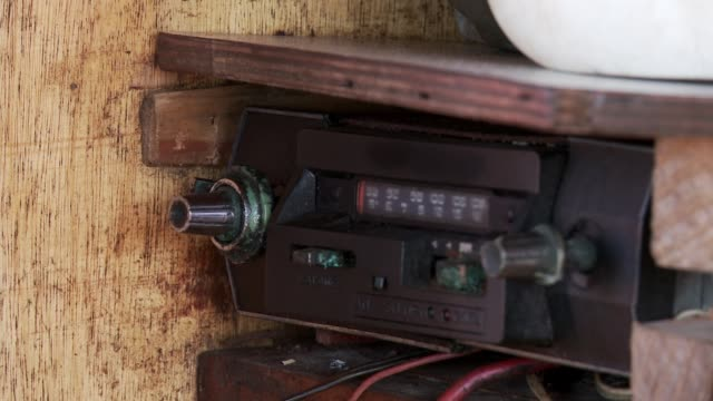 Male Hand changing Frequencies on an Old Radio Inside an Old Boat.