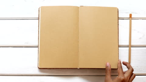 un diario di chiusura a mano maschile sulla scrivania di legno bianco, vista dall'alto e uso overhead shot per il mock up del libro modello vuoto per aggiungere qualsiasi contenuto di testo - girare video stock e b–roll