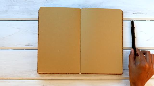 stockvideo's en b-roll-footage met een man hand nauwe dagboek boek over de witte houten bureau, bovenaanzicht en overhead schot gebruik voor lege sjabloon boek mock up elke tekstinhoud toe te voegen - magazine mockup