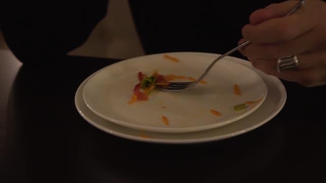 en manlig hand samlar överblivna mat från en vit tallrik med hjälp av en gaffel. resten av grönsakssallad på en tallrik man äter lätt - tallrik uppätet bildbanksvideor och videomaterial från bakom kulisserna