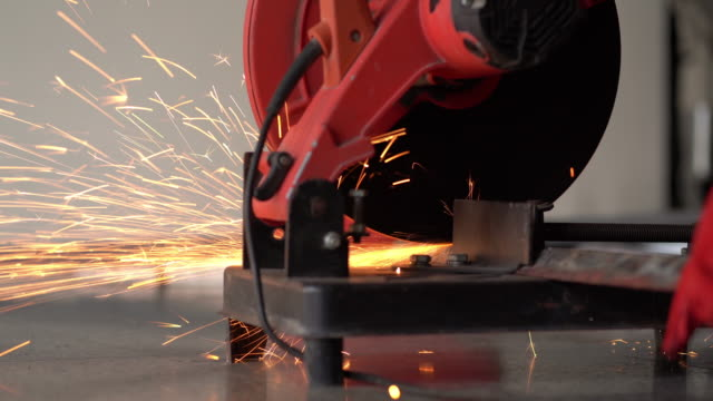 Male hand cuts off pieces of steel Male hand cuts off pieces of steel by cut off machine, cutting of a steel with steel cutting machine, splashes of sparks at construction site. sparks during. metal worker stock videos & royalty-free footage