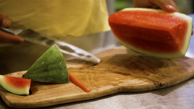 male hand cuts watermelon male hand with knife cuts watermelon. watermelon on cutting board. cooking utensil stock videos & royalty-free footage