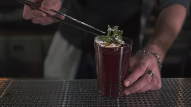 Male hand decorating fresh cocktail with mint video