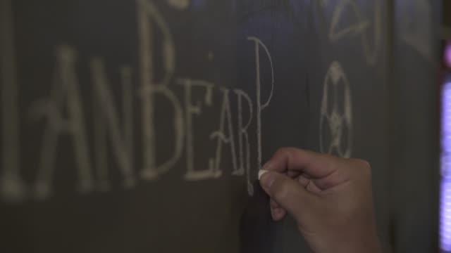 Male hand drawing chalk on black board beer menu in bar pub. Waiter writing menu on chalk board in restaurant. Drawing price in brewery bar