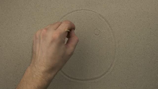 La main masculine dessine un visage symbolique heureux sur le sable d'une personne. Vue supérieure - Vidéo