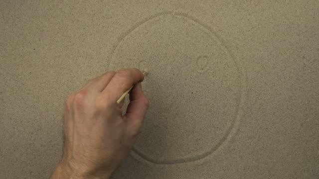 La main mâle dessine dans le sable un visage symbolique neutre d'une personne. Vue supérieure. - Vidéo