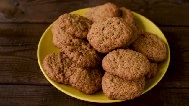 Male hand grabs a cookie Male hand grabs homemade oatmeal cookie from plate. Closeup view gripping stock videos & royalty-free footage