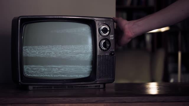 男性の手は、グリーンスクリーンで古い壊れたテレビを打つ。 - レトロ調点の映像素材/bロール