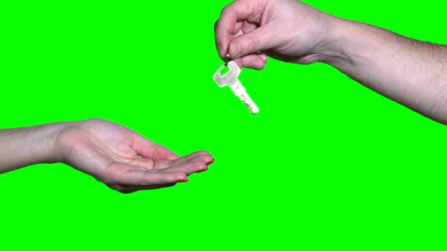 männliche hand halten wohnungsschlüssel und weibliche person isoliert auf grün übergeben - hausschlüssel stock-videos und b-roll-filmmaterial