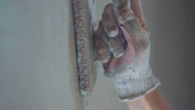 Male hand holding a plastering trowel and evening the plaster
