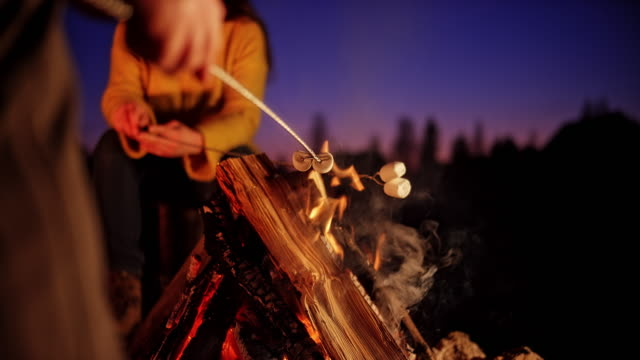SLO MO Male hand holding a skewer with marshmallow over the campfire at night
