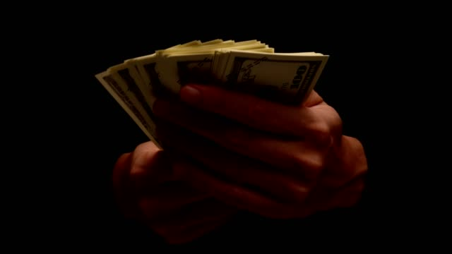 Male hand holding many banknotes isolated on black background