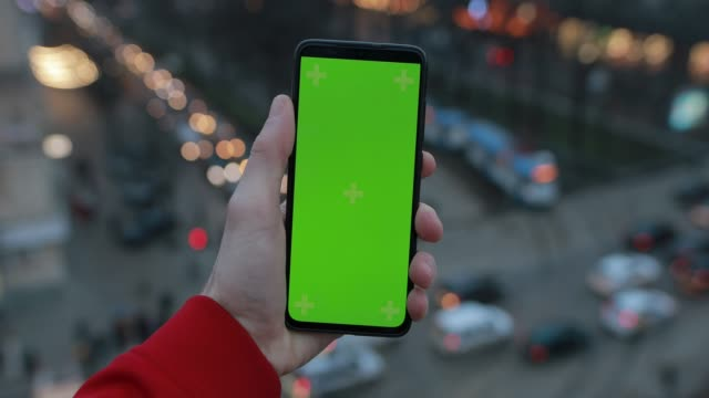 Male hand holding smartphone with green screen, car traffic background video