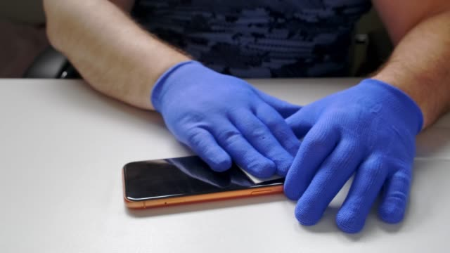 male hand in blue gloves replaces a broken tempered glass screen protector for a smartphone. A man prepares a smartphone to replace glass. Smartphone repair concept