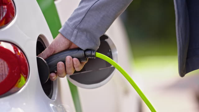 SLO MO DS Male hand inserting plug into electric car Slow motion close up shot of a male hand inserting a plug into an electric car. renewable energy stock videos & royalty-free footage