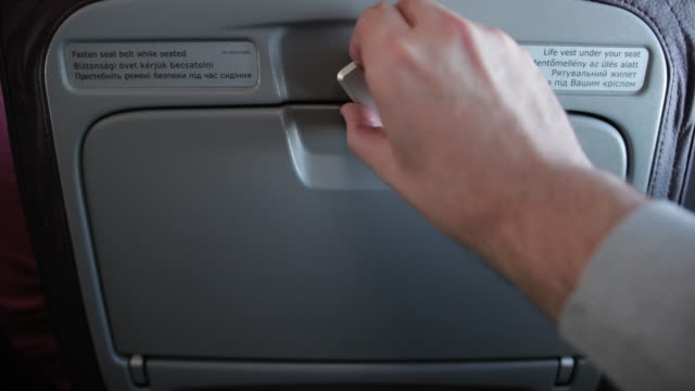 Male hand is unlocking personal food tray located on seat before him. Male hand is unlocking personal food tray located on seat before him. There are written words in three languages about seat belt and life vest. tray stock videos & royalty-free footage