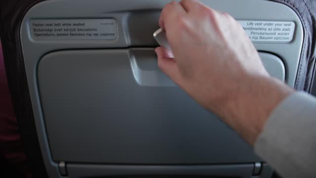 male hand is unlocking personal food tray located on seat before him. - taca filmów i materiałów b-roll