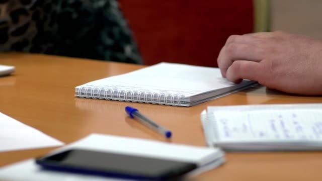 男性の手はテーブルの上に横たわるビジネス ドキュメントで書いています。 ビデオ