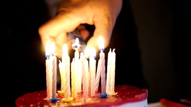 Male hand lighting a birthday candle on cake. video