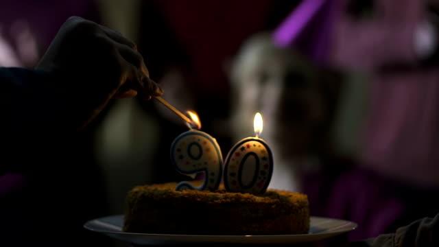 Männliche Hand Anzünden von Kerzen auf Kuchen für 90 Jahre alt Mutter Geburtstag, Familienbetreuung – Video