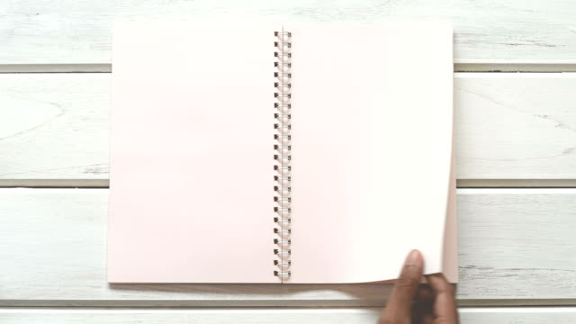 vídeos de stock e filmes b-roll de a male hand open diary paper  on the white wooden desk, top view and overhead shot use for blank template book mock up to add any text content - bloco