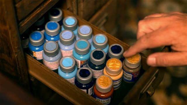 Male Hand opening a Wooden Drawer containing different Paint Jars.