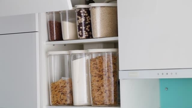 eine männliche hand öffnet und schließt einen schrank in einer modernen weißen küche ohne griffe. bestückte küche speisekammer mit lebensmitteln - pasta, buchweizen, reis und zucker. die organisation und lagerung in der küche close up - lagerraum stock-videos und b-roll-filmmaterial