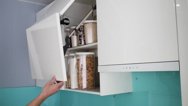 A male hand opens and closes a cabinet in a modern white kitchen without handles. Stocked kitchen pantry with food - pasta, buckwheat, rice and sugar . The organization and storage in kitchen Close up A male hand opens and closes a cabinet in a modern white kitchen without handles. Stocked kitchen pantry with food - pasta, buckwheat, rice and sugar . The organization and storage in kitchen Close up pantry stock videos & royalty-free footage
