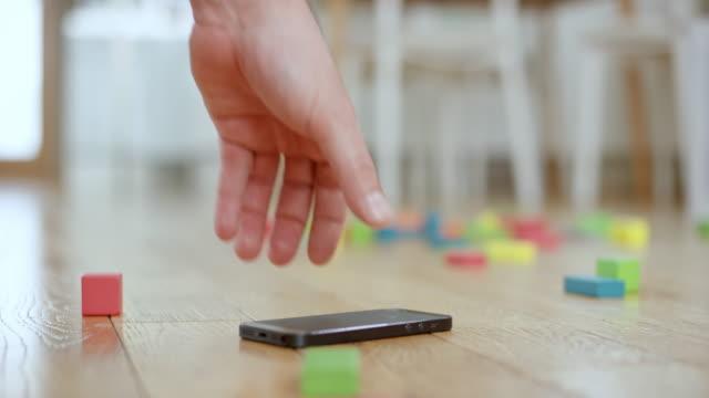 カラフルなおもちゃのブロックの間に床の上に横たわるモバイルを拾って slo mo 男性手します。 - 持ち上げる点の映像素材/bロール
