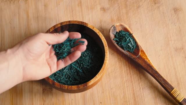 Male Hand picks up Spirulina Algae Flakes video