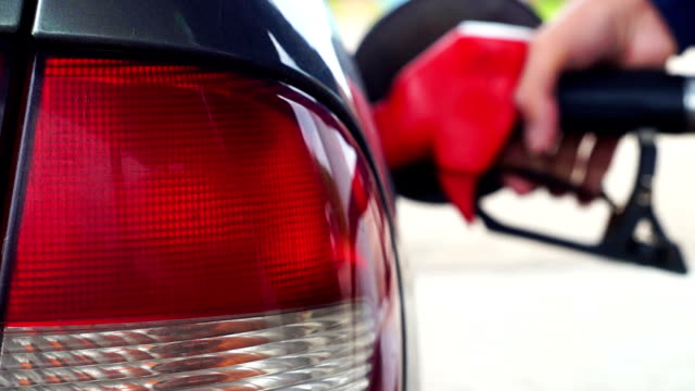Male hand refueling a car on gas station