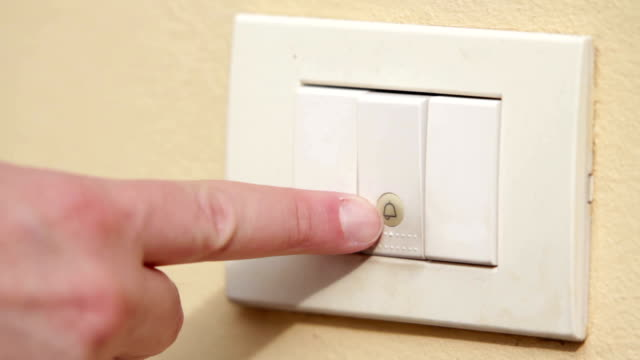 Male hand ringing a white electric doorbell insistently