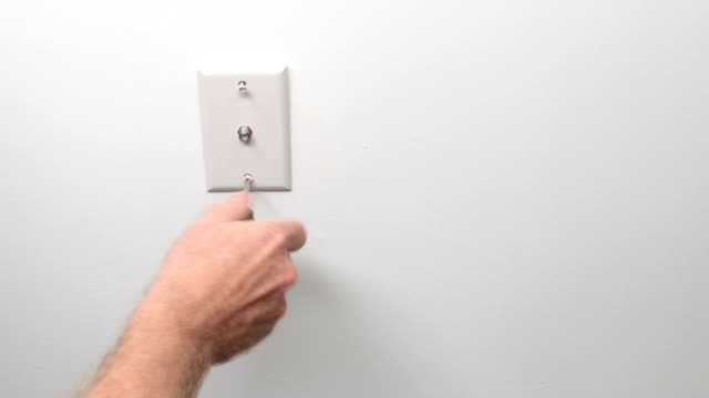Male Hand Screwing in a Cable Outlet in a White Wall video
