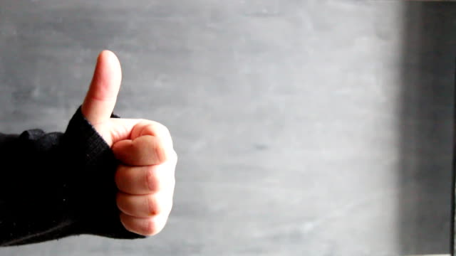 male hand showing thumbs up sign against gray background video