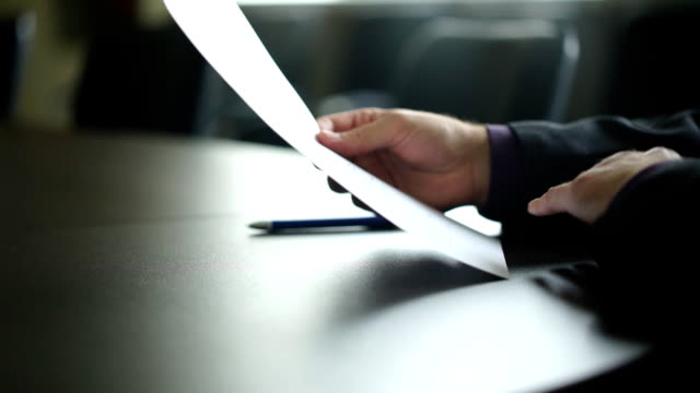 male hand signing contract or subscription form with a pen on a rustic wooden desk video