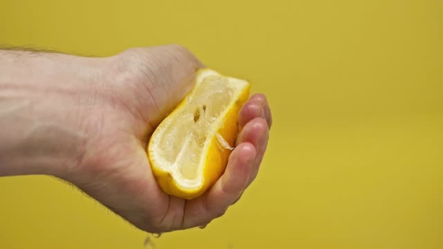 male hand squeezing lemon isolated on yellow, slow motion - сжимать стоковые видео и кадры b-roll