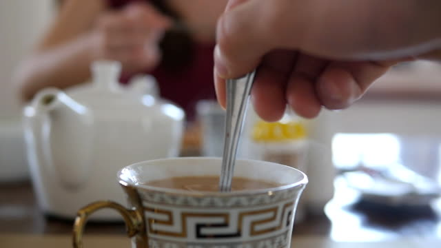 Male hand stirring sugar or milk in a cup of hot coffee or tea. Slow motion Close up