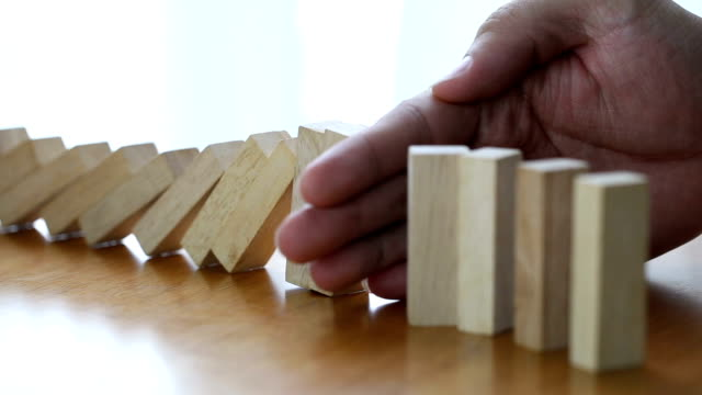 Male hand stopping the domino effect. Risk control concept video