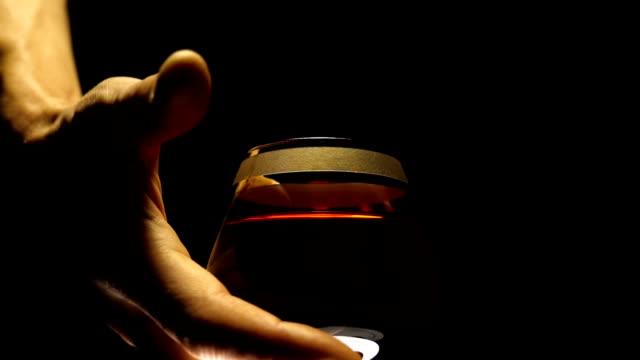 männliche hand nimmt ein glas rotwein auf schwarzem hintergrund - cabernet sauvignon traube stock-videos und b-roll-filmmaterial