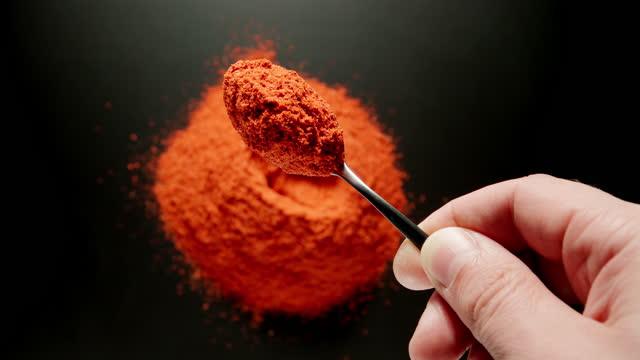 vídeos y material grabado en eventos de stock de mano masculina tomando una cucharadita de polvo de pimiento rojo de una pila, vista superior - cayena guindilla roja