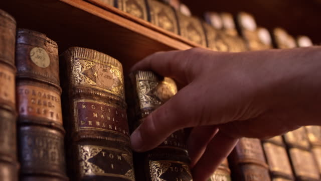 DS Male hand taking an old book from the shelf