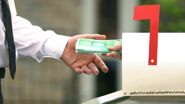 Male hand taking euro banknotes from mail box, remittance service money transfer