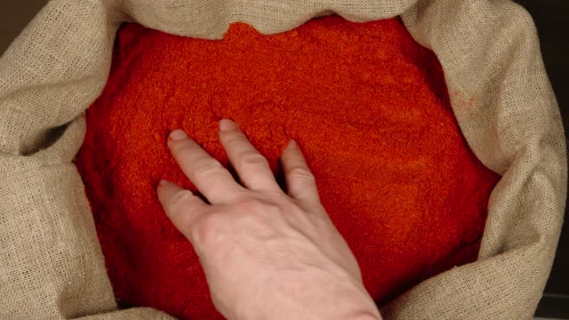TOP VIEW: Male hand touching a red pepper powder in a sac TOP VIEW: Male hand touching a red pepper powder in a sac paprika stock videos & royalty-free footage